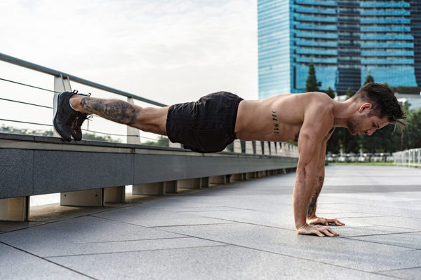 Flexiones de brazos con apoyo elevado de los pies flexion en L